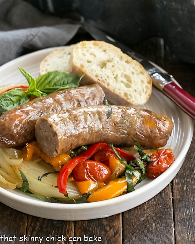 Sheet Pan Sausage and peppers served on a white dinner plate with a slice of rustic bread and a red handled fork