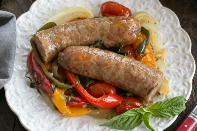 Overhead view of sausage and peppers on a decorative white plate