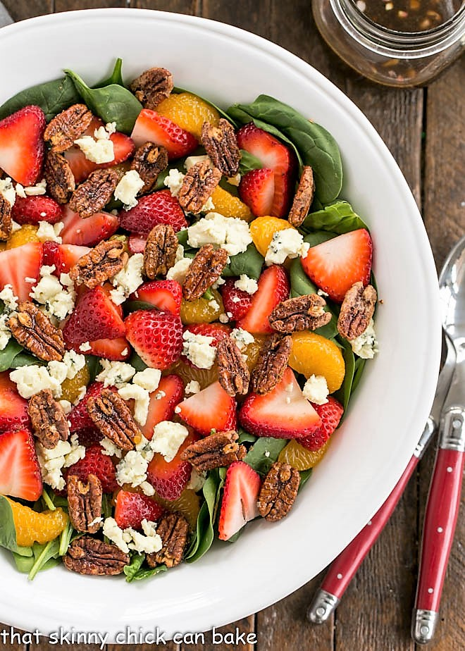 Overhead view of strawberry spinach salad in a white serving bowl