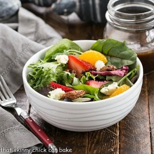 Spinach Strawberry Salad in a white bowl with a red handled fork