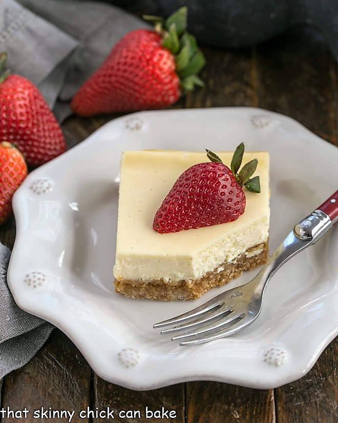 One cheesecake bar topped with a half strawberry on a decorative white plate with a fork