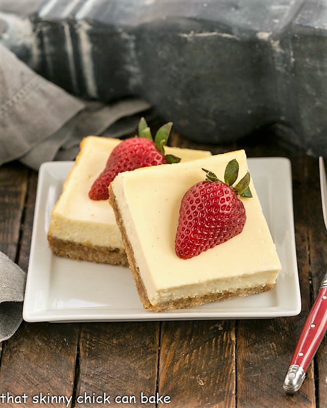 Overhead view of two vanilla bean cheesecae bars topped with strawberry halves