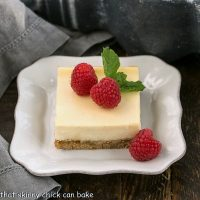 One vanilla cheesecake bar on a white plate topped with raspberries and a sprig of mint