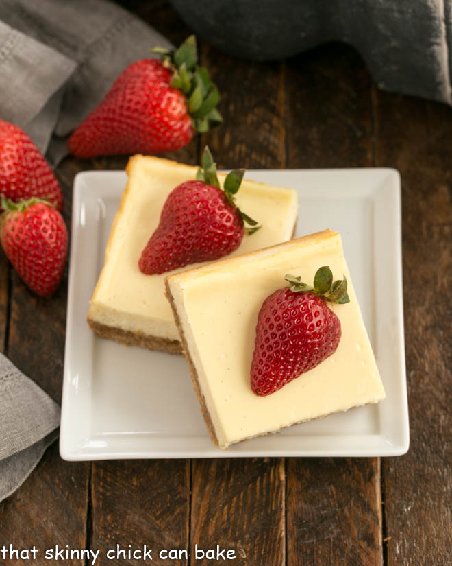 two cheesecake bars topped with strawberries on a square white plate
