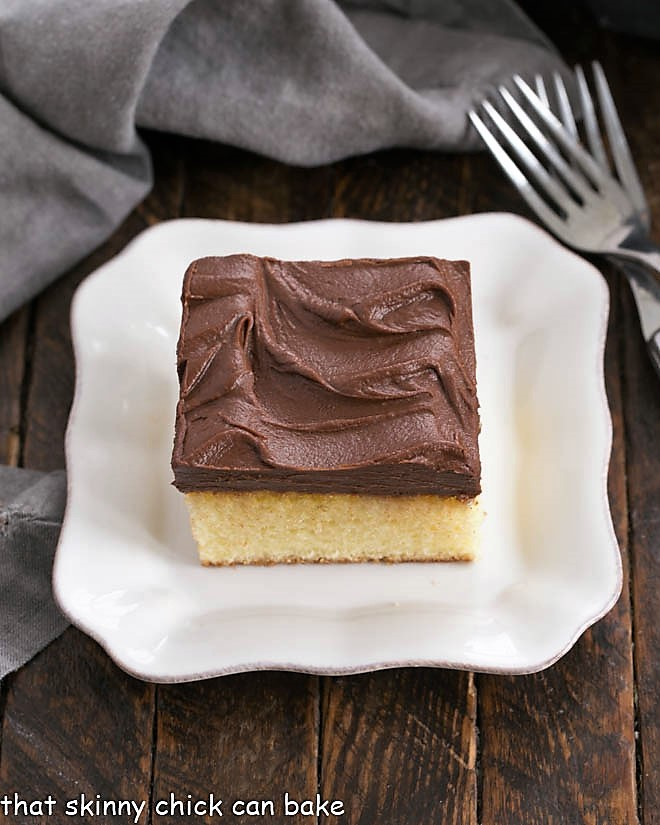 Overhead shot of a square of yellow snack cake on a square white dessert plate