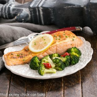Oven roasted salmon topped with a lemon slice on a white plate with broccoli