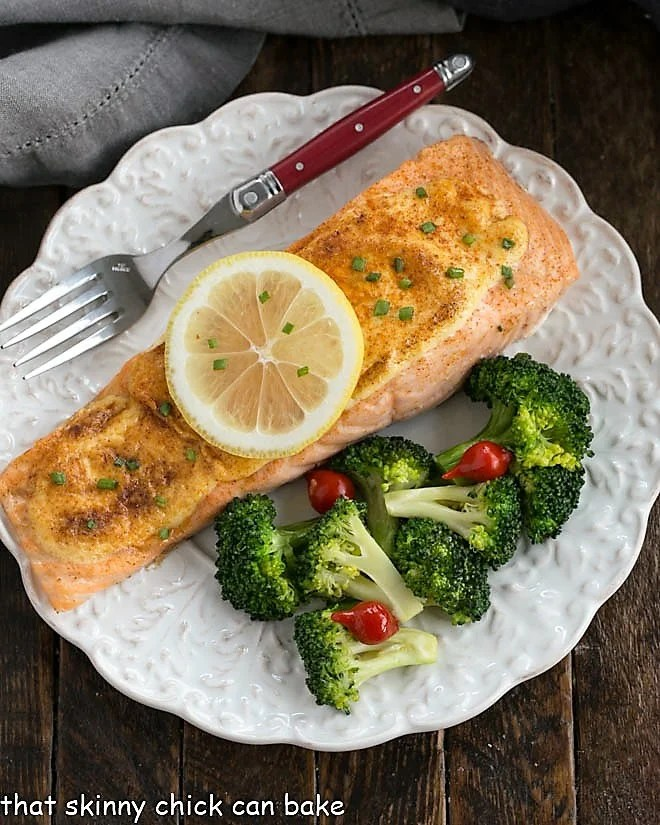 Overhead view of Roasted Salmon topped with a lemon slice on a white plate with broccoli