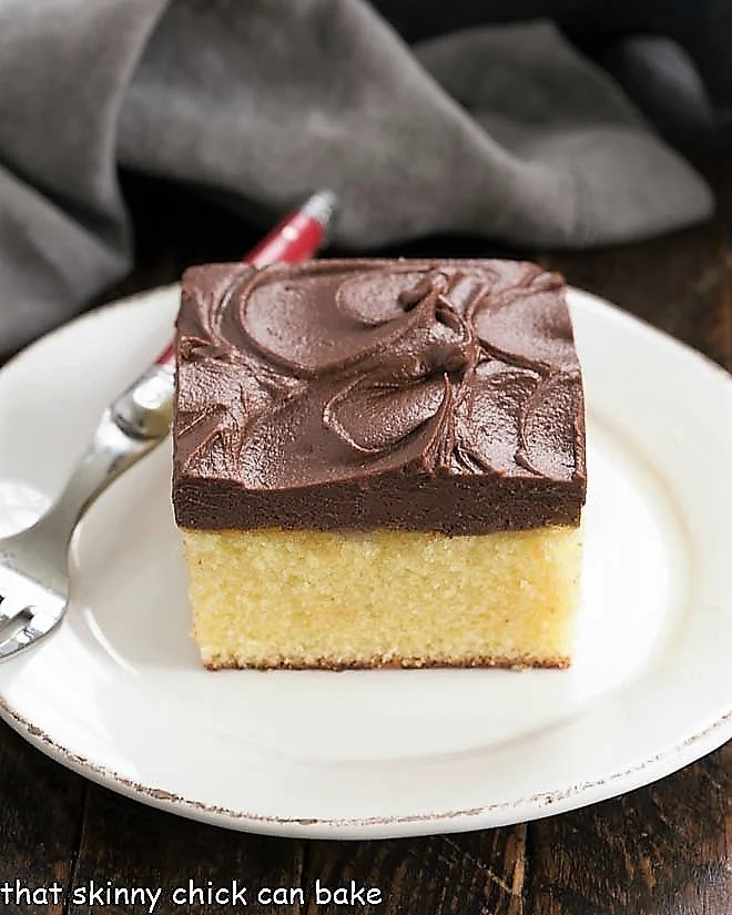 Yellow snack cake slice on a white plate with a red handle fork