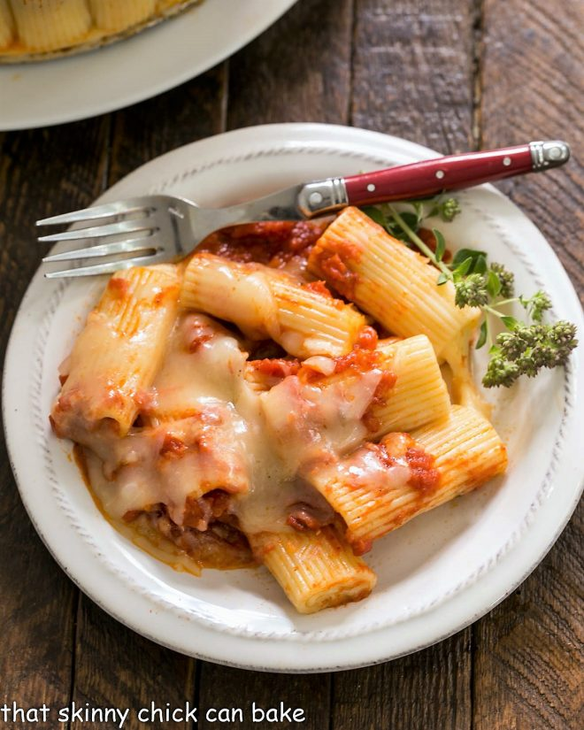 Overhead view of baked rigatoni on a small wite plate with a fork and herb garnish
