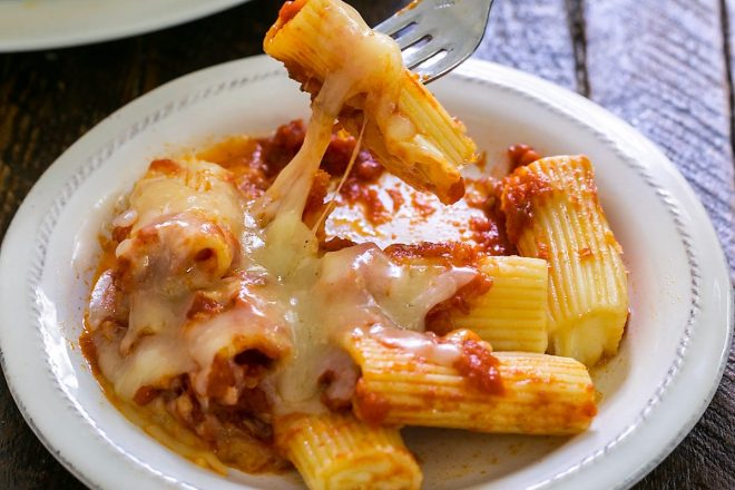 Baked rigatoni on a plate with a fork lifting up a noodle