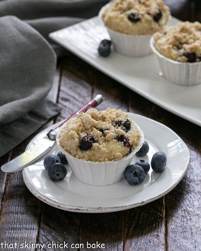 Blueberry cream cheese muffin on a white plate with a knife and fresh blueberries