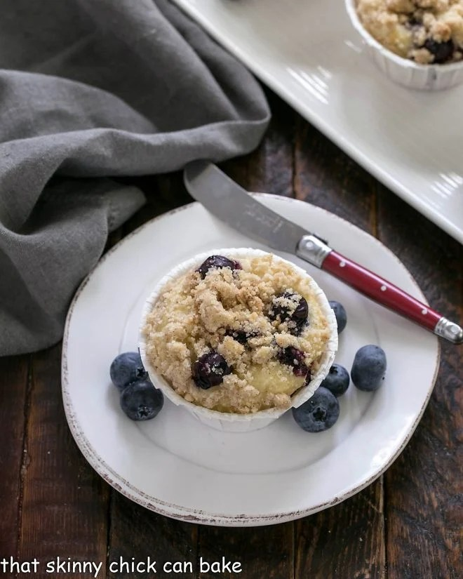 Overhead view of a blueberry muffin on a white plate with a red handle knife