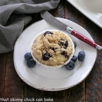 Overhead view of streusel topped blueberry muffin on a round white plate garnished with fresh blueberries and flanked with a red handle knife