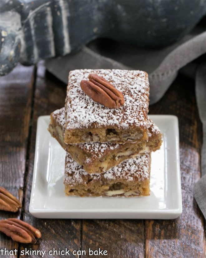 3 pecan bars stacked on a square white plate