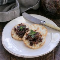 Bacon jam on crackers on a white appetizer plate