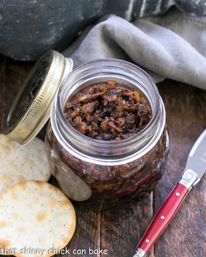 a jar of baon jame with crackers and a red handled knife