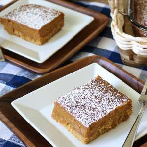 Two Slices of Pumkin Gooey Butter Cake plated with the full cake sheet in the background