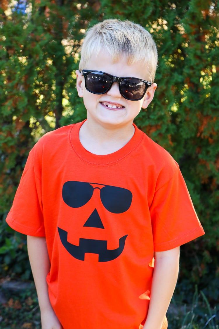 Boy sporting Orange Jack-o-lantern Shirt with sunglasses on