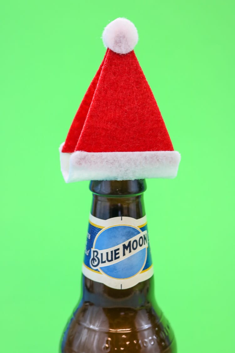 """Add the Santa Hats to Tops of Bottles to create a fun """"gift wrap"""" idea for a 6 pack"""