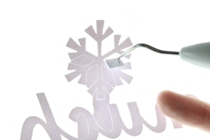 Weeding insides of snowflakes from glitter iron on with BrightPad