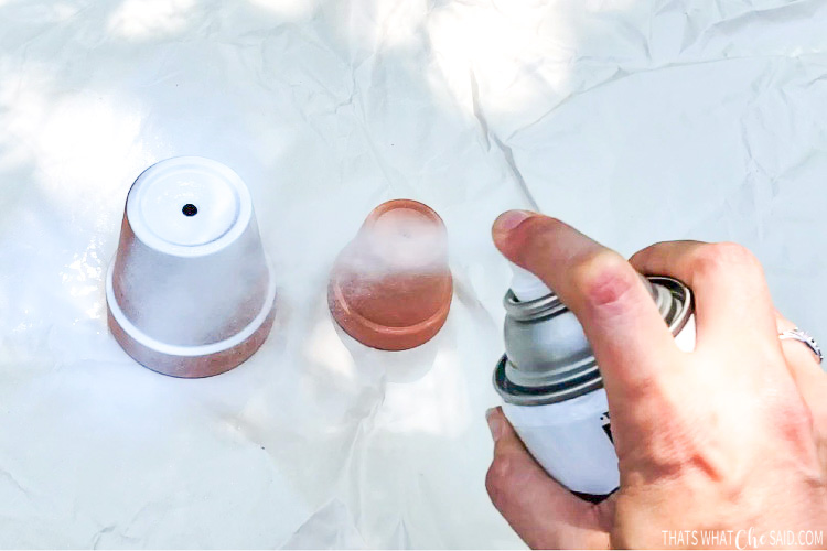 Clay pots being spray painted white