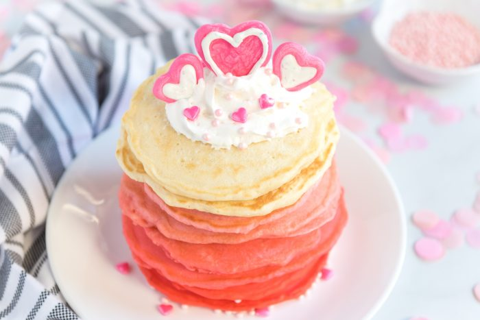 Ombre Valentine Pancakes Stacked on a plate with chocolate candy melt heart design on top with whipped topping.