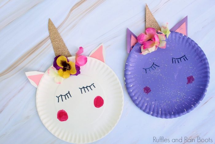 Paper plates painted as sleeping unicorns with flowers and sparkly horns.