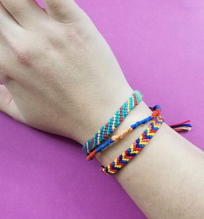 Three different friendship bracelets on a wrist.