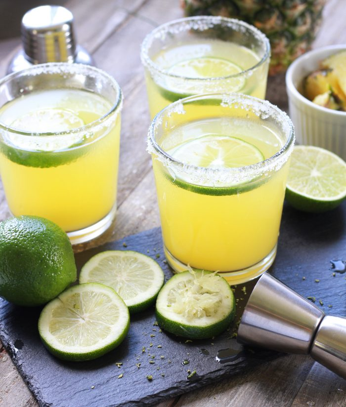 Three Pineapple Margaritas with sliced limes and fresh cut pineapple - Square Format