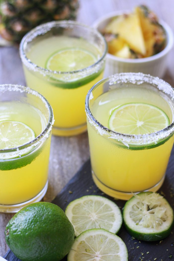 Three Pineapple Margaritas with sliced limes and fresh cut pineapple