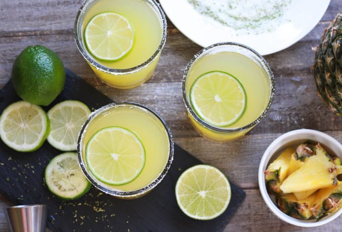 Three Pineapple Margaritas with sliced limes and fresh cut pineapple with salt and shot jigger