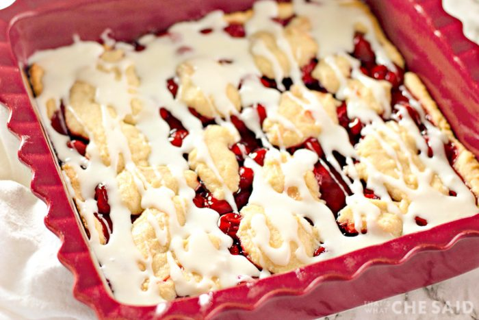 Homemade Cherry Bars in Baking Dish with frosting drizzle - Angled Shot