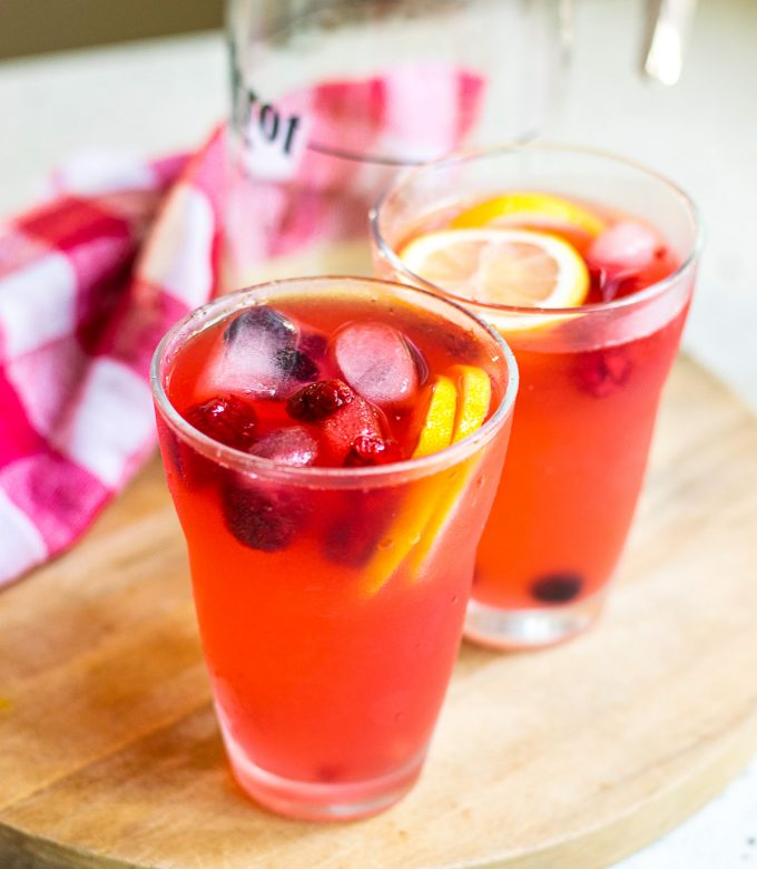 Two cups and a pitcher of finished berry lemonade.