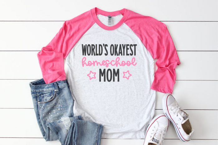 """White Raglan T-shirt with Pink sleeves and jeans and sneakrs. Shirt reads """"World's Okayest Homeschool Mom"""" in iron on vinyl - Horizontal Format"""