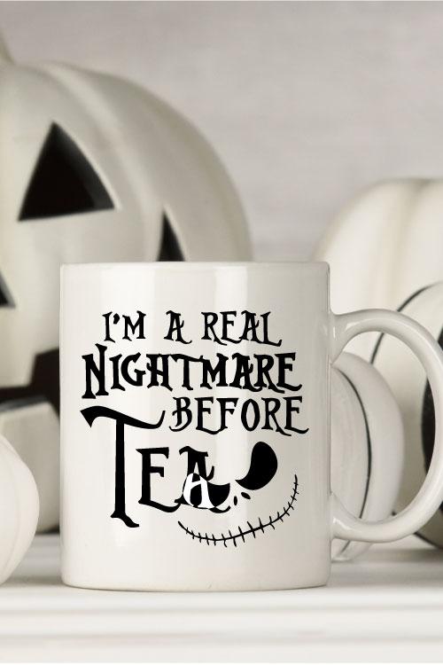 "White mug with black and white halloween decor behind. Mug Reads"" I'm a Real Nightmare Before Tea"""