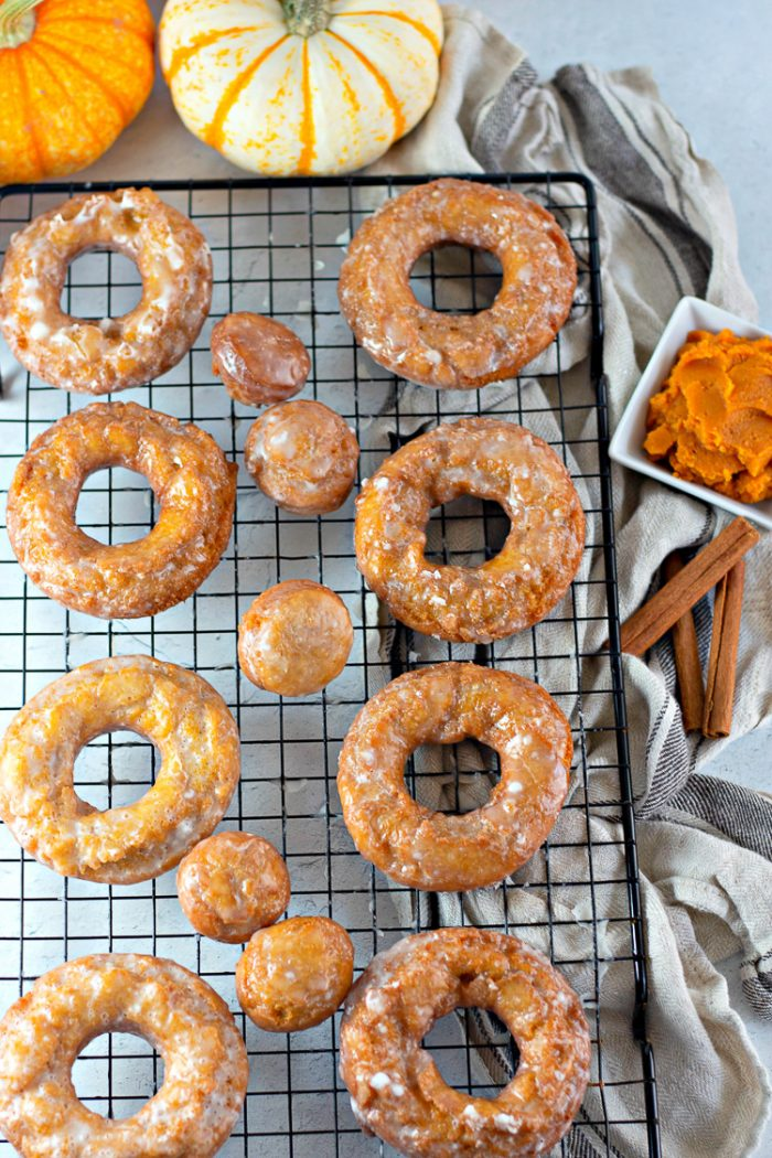 Pumpkin donuts and pumpkin donut holes on a black wire cooling rack with pumpkins, pumpkin puree and cinnamon sticks