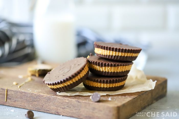 Close up of homemade peanut butter cups on small wooden board with milk in background
