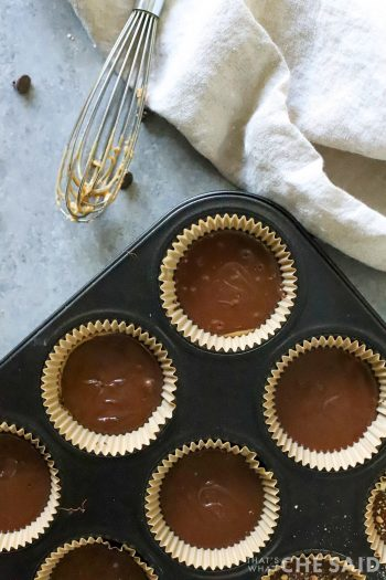 Cupcake tin with liners topped off with chocolate over peanut butter