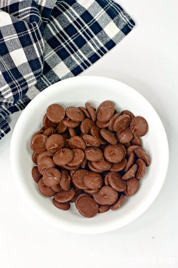 Melting chocolates in a white bowl with black plaid cloth napkin