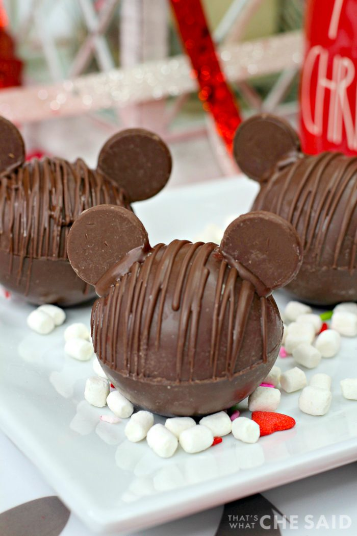 Three Chocolate Hot Chocolate Bomb with added chocolate wafers as ears to resemble Mickey Mouse with marshmallows and Christmas decor in background vertical orientation 45 degrees angle