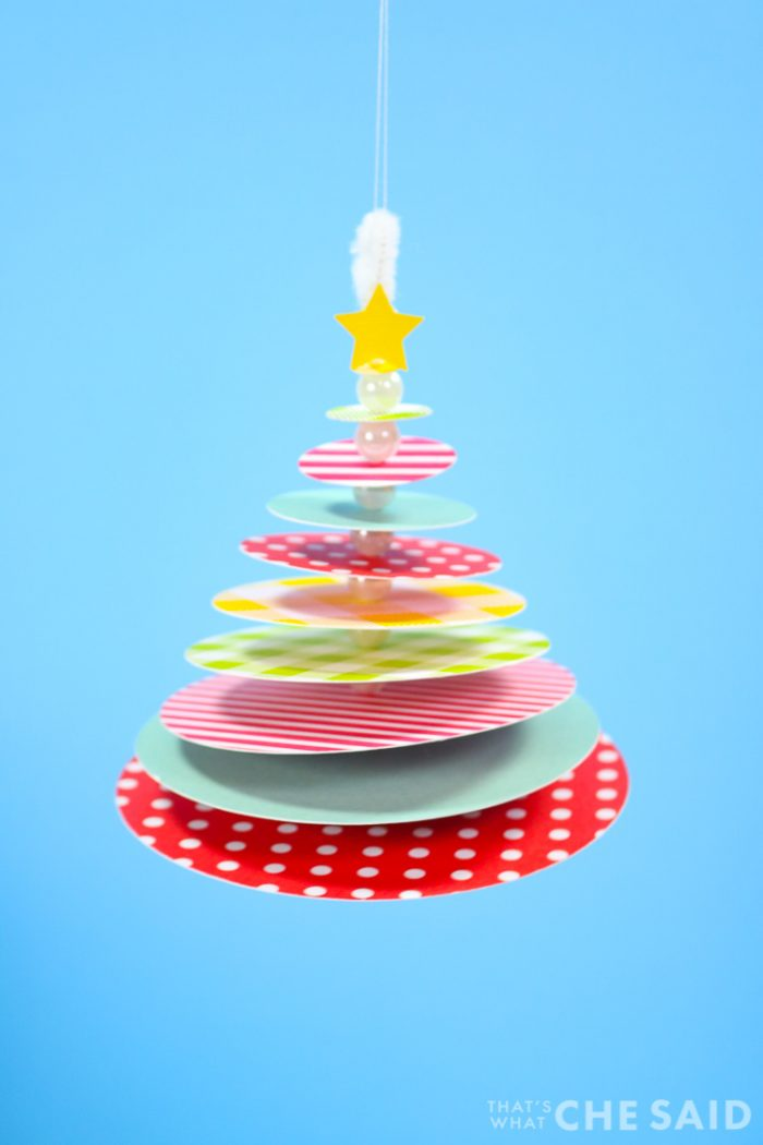 Finished Paper Christmas Tree Ornament Hanging against solid blue background