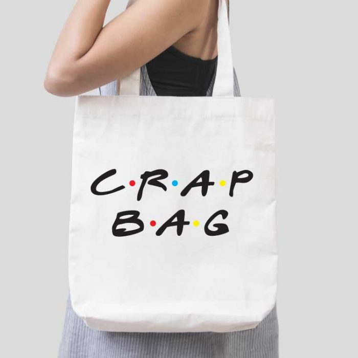 """Woman holding white tote bag with """"Crap Bag"""" in FRIENDS tv show font applied with iron on"""