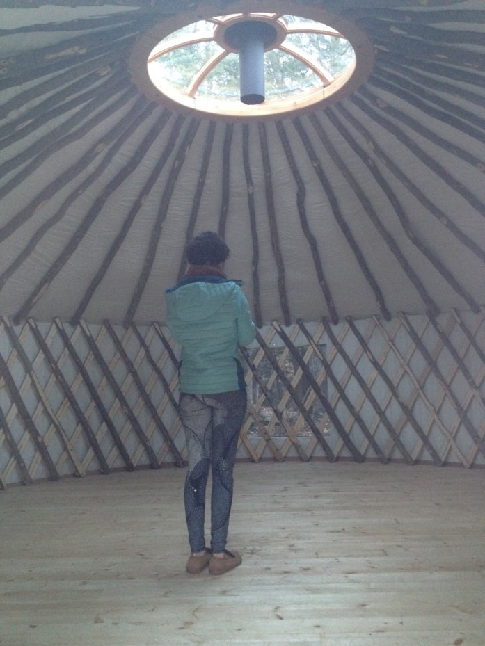 The empty interior of our new yurt, with skylight, chimney, sapling rafters, lattice walls, and eastern pine floors.