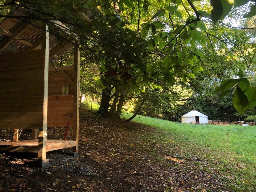 View of outdoor shower with off grid yurt in the background