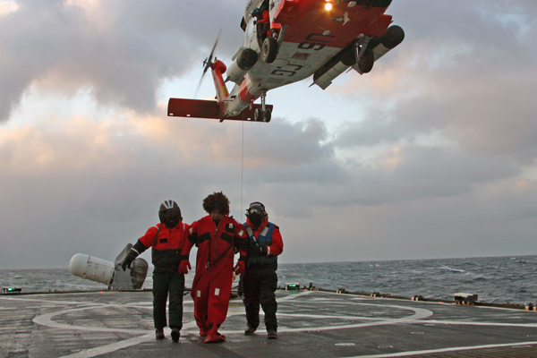 A Coast Guard rescue team recieves a survivor on board the Coast Guard Cutter Munro. The Alaska Ranger began taking on water 120 miles west of Dutch Harbor March 23, 2008.(U.S. Coast Guard Photo by CGC Munro)