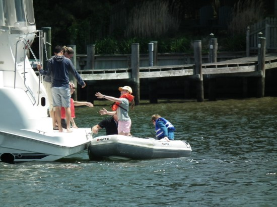 A helping hand. From tender to cruiser in the harbor at St. Michael's, Md. THE CHESAPEAKE TODAY photo
