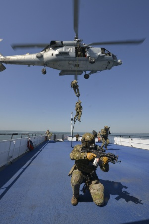 Coast Guard Maritime Security Response Team member provides cover during helicopter fast rope boarding