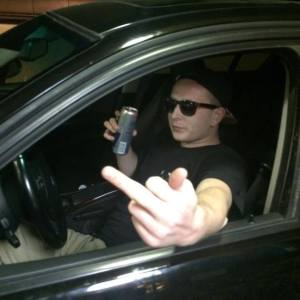 JAMES-C.-PAVLIKOWSKI-with-beer-in-car-and-finger. Pavlikowski posted numerous photos of himself in similar poses and lamented not having a car to drive.