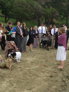 image of a gathering on a beach with an 8 year old in a camping chair and white baptism outfit and her mother in front of her giving a talk