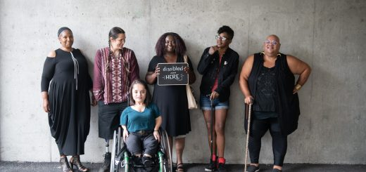 "Six disabled people of color smile and pose in front of a concrete wall. Five people stand in the back, with the Black woman in the center holding up a chalkboard sign reading ""disabled and here."" A South Asian person in a wheelchair sits in front."